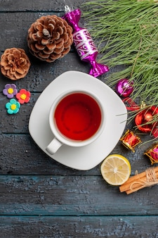 Top view a cup of tea cinnamon lemon spruce branches with christmas toys and cones next to the cup of tea on the white saucer on the table