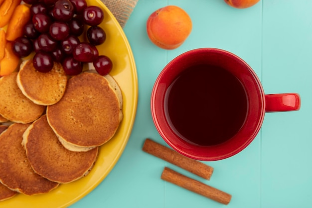 Top view of cup of tea and cinnamon and pancakes with cherries and apricot slices in plate and apricot on blue background