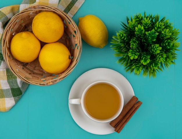 Top view of cup of tea and cinnamon on saucer with basket of lemons on plaid cloth on blue background