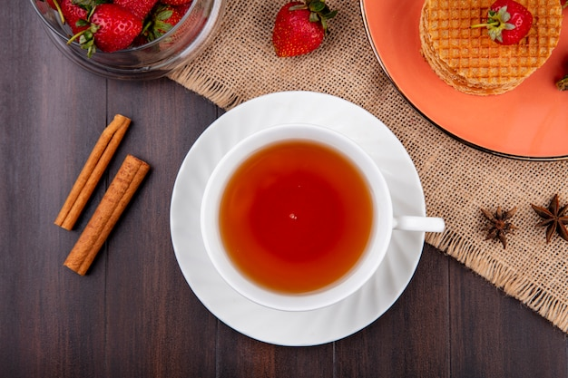 Top view of cup of tea and cinnamon with waffle biscuits and strawberries in plate and bowl on sackcloth on wood