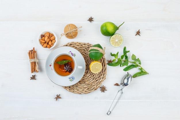 Vista dall'alto una tazza di tè, agrumi e foglie di menta sulla tovaglietta rotonda con lime