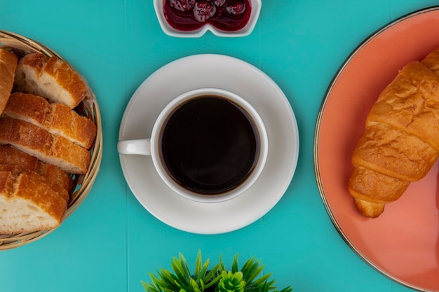 Top view of cup of tea and croissant sliced baguette with raspberry jam and plant on blue background