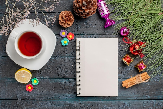 Top view a cup of tea a cup of black tea on the white saucer next to the white notebook lemon cinnamon sticks spruce branches with christmas toys and cones on the grey background