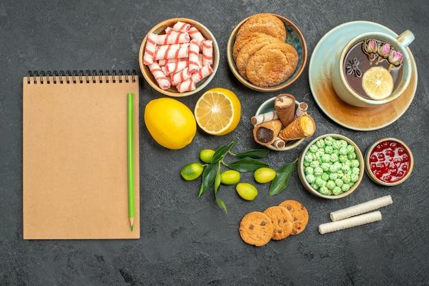 Vista dall'alto una tazza di tè una tazza di tisana agrumi dolci biscotti marmellata notebook matita