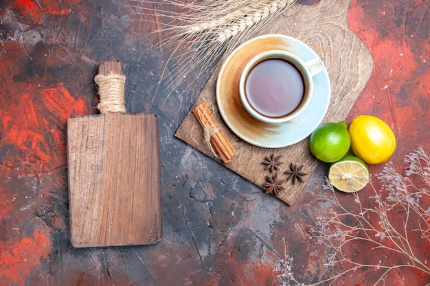 Top view a cup of tea a cup of tea star anise lemon cinnamon next to the wooden board and branches