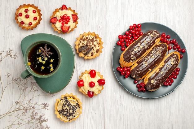 Vista dall'alto una tazza di tè e biscotti diversi a sinistra e bignè al cioccolato e ribes sul piatto grigio sul lato destro del tavolo di legno bianco