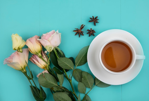 Top view of cup of tea and flowers on blue background