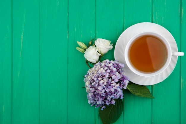 Top view of cup of tea and flowers on green background with copy space