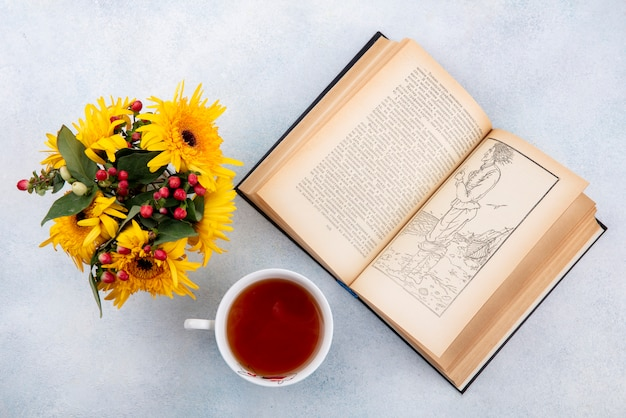 Top view of cup of tea and flowers with open book on white