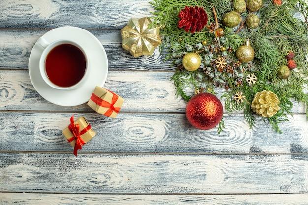 Vista dall'alto una tazza di tè regali rami di abete su fondo di legno