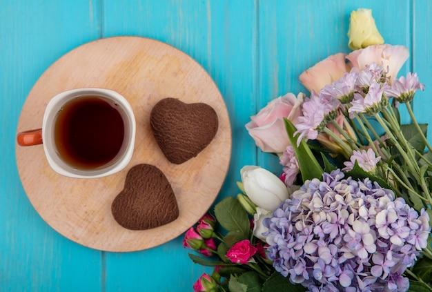 Top view of cup of tea and heart-shaped cookies on cutting board with flowers on blue background