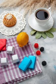 Vista dall'alto della tazza di tè caldo all'interno della tazza bianca con cioccolatini al limone sulla scrivania leggera, torta di caramelle al cioccolato e tè