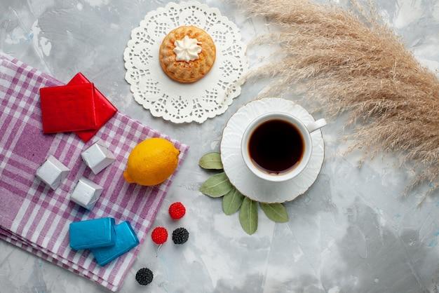 Vista dall'alto della tazza di tè caldo all'interno della tazza bianca con cioccolatini al limone sulla luce, torta di caramelle al cioccolato del tè