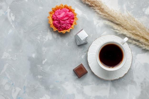 Vista dall'alto della tazza di tè caldo con cioccolato e torta sulla luce, tè al cioccolato caramelle biscotto