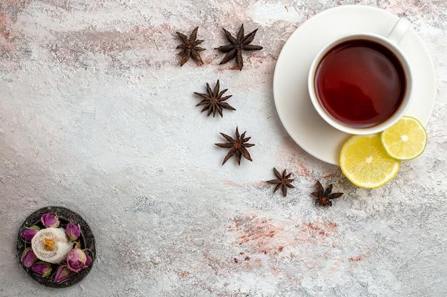Vista dall'alto tazza di tè all'interno della tazza e piatto con il limone su sfondo bianco tè bevanda dolce colazione cerimonia