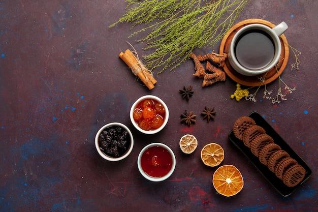 Vista dall'alto tazza di tè all'interno del piatto e tazza su sfondo scuro bevanda del tè foto a colori dolce
