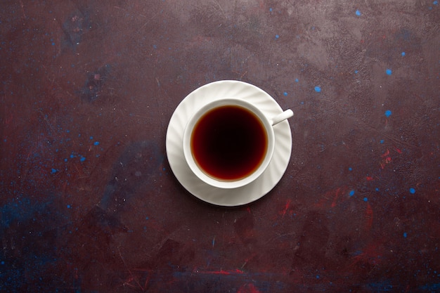 Top view cup of tea inside plate and cup on dark background tea drink color photo sweet