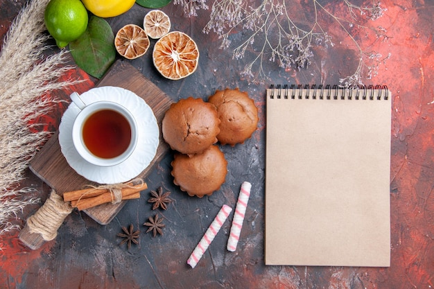 Top view a cup of tea lemon cinnamon a cup of black tea on the cutting board white notebook