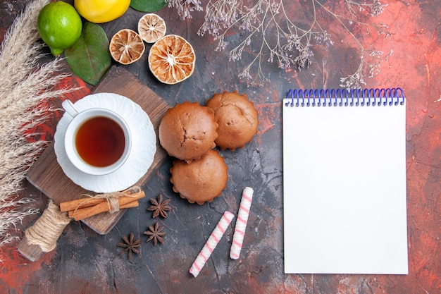 Top view a cup of tea lime lemon cinnamon a cup of black tea on the board white notebook