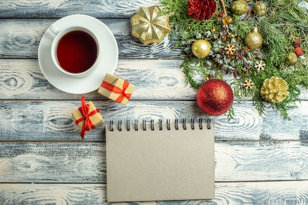 Top view a cup of tea a notebook gifts fir tree branches on wooden background
