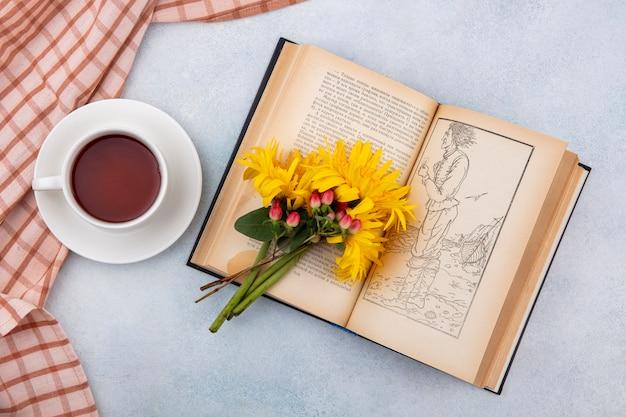 Vista dall'alto della tazza di tè sul panno plaid e fiori sul libro aperto su bianco
