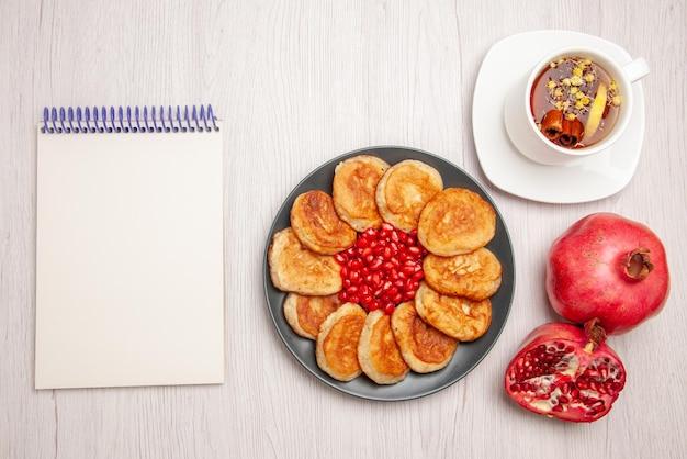 Vista dall'alto una tazza di tè piatto di frittelle e semi di melograno una tazza di tisana con limone e melograno accanto al taccuino bianco sul tavolo