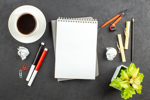 Vista dall'alto tazza di tè rosso e nero pennarelli raccoglitore clip bussole notebook sul tavolo nero