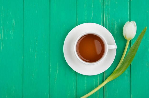 Top view of cup of tea on saucer and flower on green background with copy space