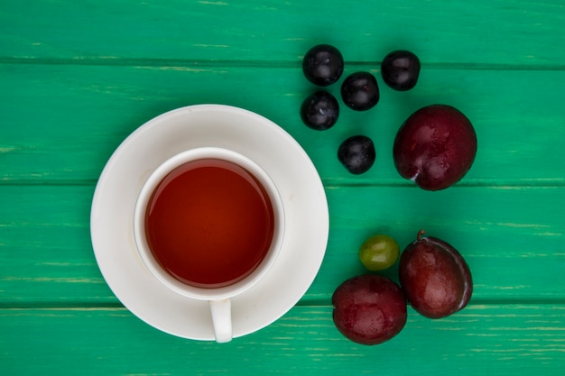 Top view of cup of tea on saucer and pattern of fruits as pluots grape berrie and sloe berries on green background