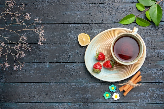 Top view a cup of tea and strawberries on saucer slice of lemon cinnamon flower candies leaves on the dark wooden table