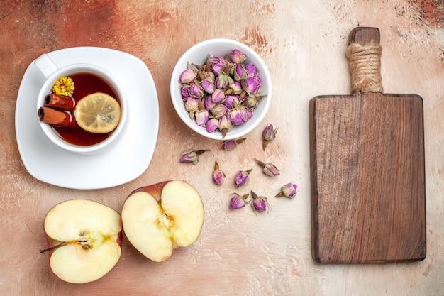 Vista dall'alto tazza di tè con mele e fiori sul fiore del tè alla frutta del pavimento chiaro