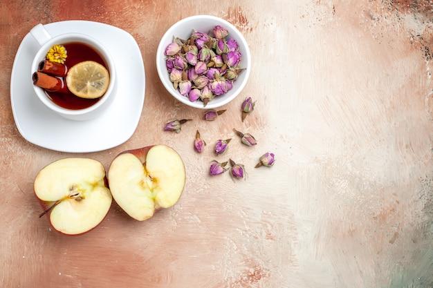 Vista dall'alto tazza di tè con mele e fiori sul fiore del tè alla frutta da tavolo luminoso