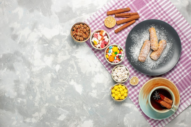 Top view of cup of tea with bagels and candies on white surface