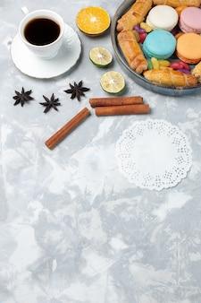Vista dall'alto tazza di tè con bagel e macarons sulla scrivania bianca