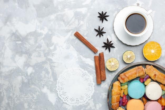 Vista dall'alto tazza di tè con bagel e macarons su bianco