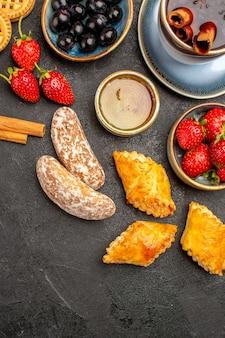 Vista dall'alto tazza di tè con biscotti e frutta sulla torta di frutta biscotto dolce scrivania scuro