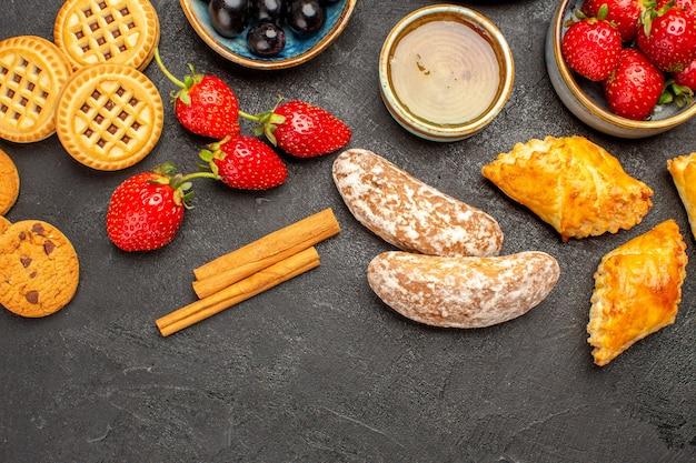 Vista dall'alto tazza di tè con biscotti e frutta sulla torta di frutta biscotto dolce pavimento scuro