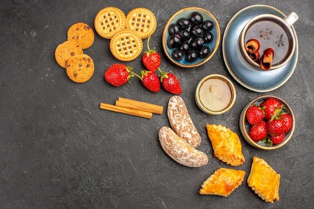 Vista dall'alto tazza di tè con biscotti e frutta sulla torta di frutta biscotto dolce superficie scura