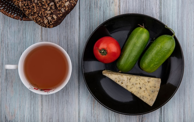 Top view cup of tea with black bread  cheese  cucumber and tomato on plate on gray background