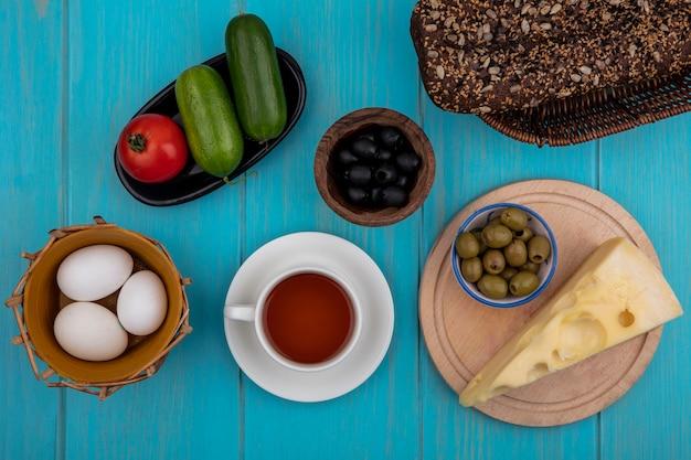 Vista dall'alto tazza di tè con cetrioli formaggio pane nero e pomodoro e olive con uova di gallina su sfondo turchese