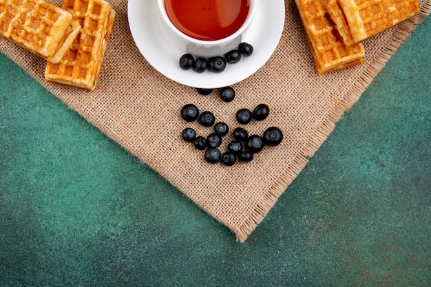 Top view cup of tea with blueberries and waffles on a green background