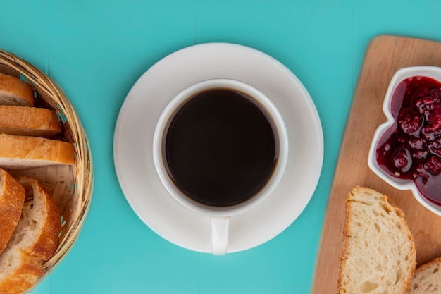 Top view of cup of tea with bread slices and raspberry jam on cutting board on blue background