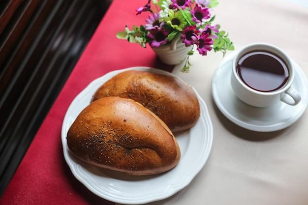 Vista dall'alto tazza di tè con panini sul tavolo e con fiori