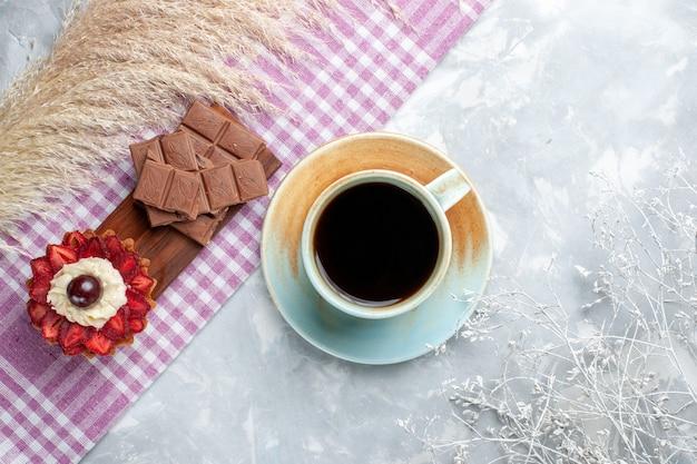 Vista dall'alto tazza di tè con torta e barrette di cioccolato sulla scrivania bianca torta di zucchero dolce al cioccolato
