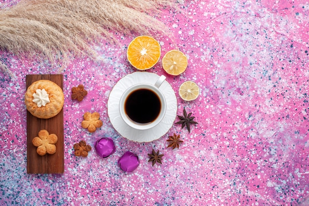 Vista superiore della tazza di tè con fette di arancia torta e biscotti sulla superficie rosa Foto Gratuite