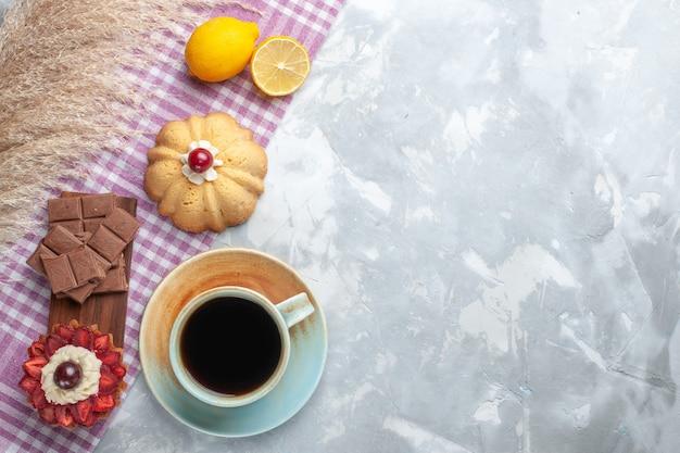 Vista dall'alto tazza di tè con torta al limone e barrette di cioccolato sulla scrivania bianca torta dolce al cioccolato
