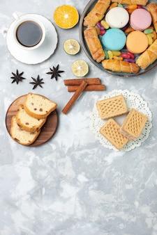 Vista dall'alto tazza di tè con fette di torta e bagel su bianco