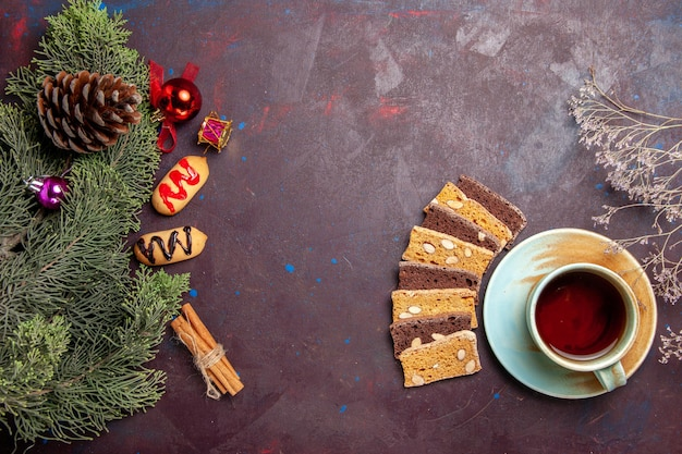 Vista dall'alto tazza di tè con fette di torta e biscotti su uno spazio buio