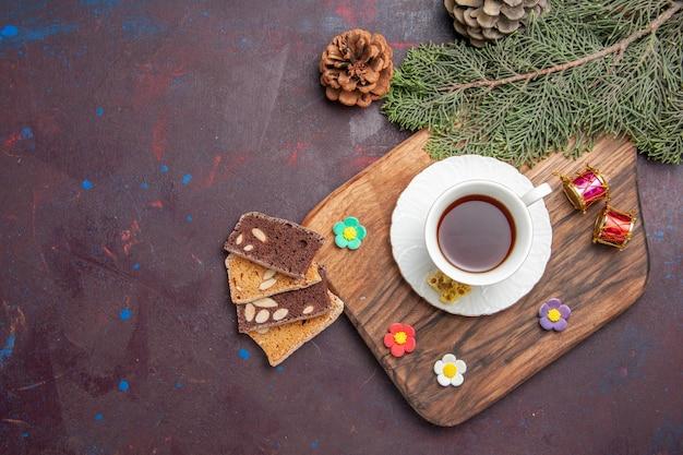 Vista dall'alto tazza di tè con fette di torta nello spazio buio