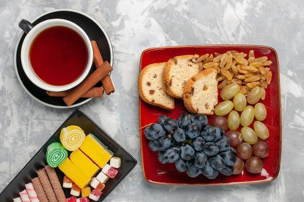 Vista dall'alto tazza di tè con fette di torta uva e biscotti sulla superficie bianca